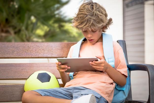 Schoolkind met een tablet heeft een rugzak met boeken, wacht om de school binnen te gaan waar hij studeert