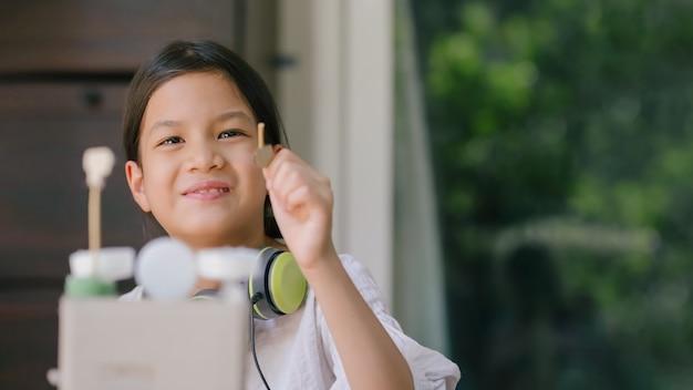 Schoolkind met gerecyclede en upcycled ambachten. recycling helpt de planeet te redden, kinderen leren om minder afval te produceren. creatieve activiteiten voor kinderen.