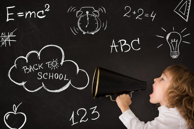 Schoolkind schreeuwt door megafoon tegen schoolbord onderwijsconcept terug naar school
