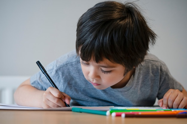 Schoolkind tekening en kleuren op wit papier, kind thuis werk thuis te doen.