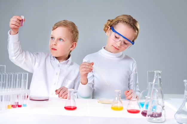 Schoolkinderen analyseren van reageerbuizen met vloeistoffen