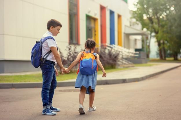 Schoolkinderen, broer en zus met rugzakken hand in hand gaan 's ochtends op een zonnige dag naar school.