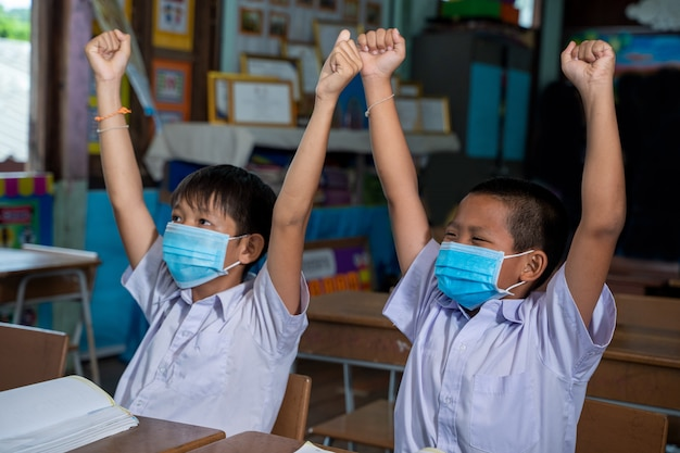 Schoolkinderen die een beschermend masker dragen om te beschermen tegen covid-19 leren in de klas, onderwijs, basisschool.