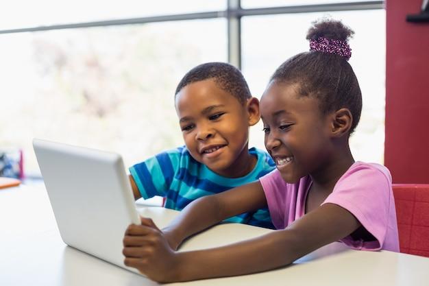 Schoolkinderen die een digitale tablet in klaslokaal gebruiken