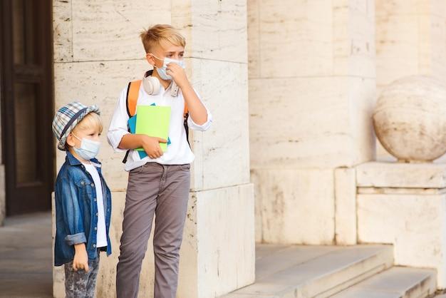 Schoolkinderen die een gezichtsmasker dragen tijdens de uitbraak van het coronavirus.