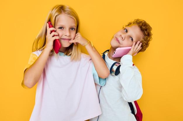Schoolkinderen die een smartphone onderzoeken en het onderwijsconcept van de spelstudio spelen