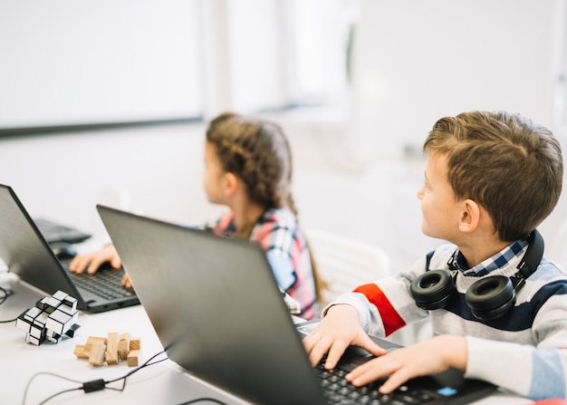 Schoolkinderen die met laptop zitten die bord bekijken