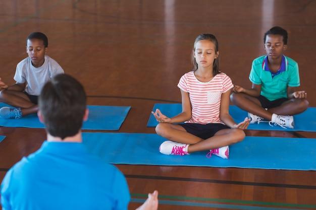 Schoolkinderen en leraar mediteren tijdens yogales