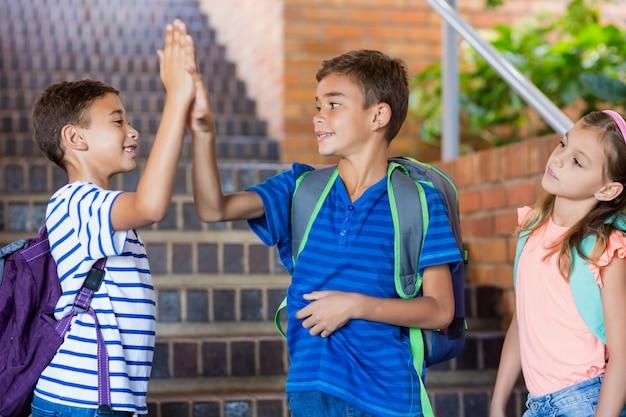 Schoolkinderen geven high five op trap