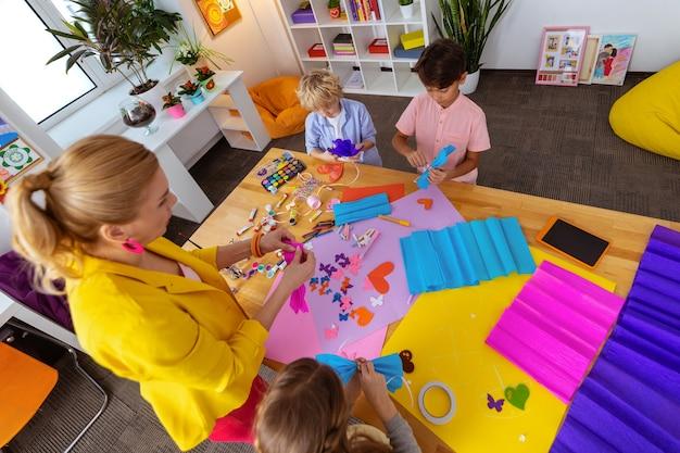 Schoolkinderen helpen. leraar in gele jas helpt schoolkinderen met het maken van uitsnijdingen en decoraties