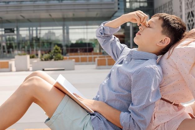 Schoolkinderen jongen tieners 11 jaar oud studeren op schoolplein, zitten op de bank, schooljongen is moe