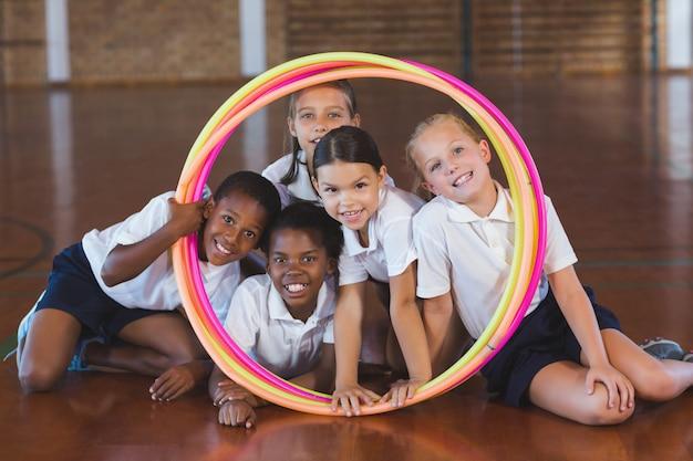 Schoolkinderen kijken door hoelahoep in basketbalveld