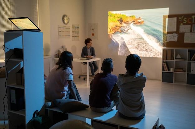 Schoolkinderen kijken naar film over natuurlijke omgeving