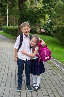 Schoolkinderen knuffelen elkaar in het park