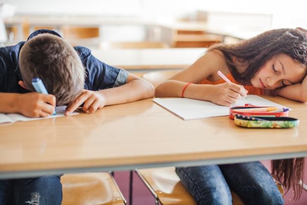 Schoolkinderen leunend op tafel slapen