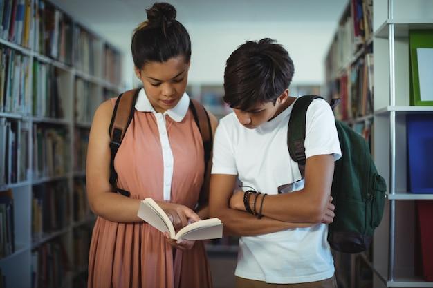 Schoolkinderen lezen van boeken in bibliotheek op school
