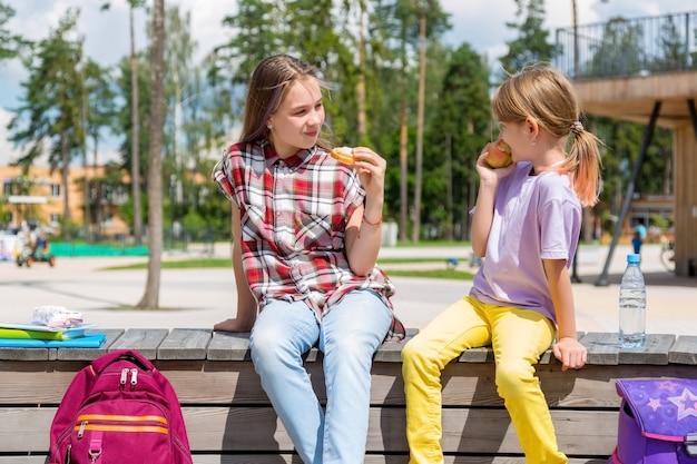 Schoolkinderen lunchen samen buiten het gebouw. meisjes in tuin die lunch delen