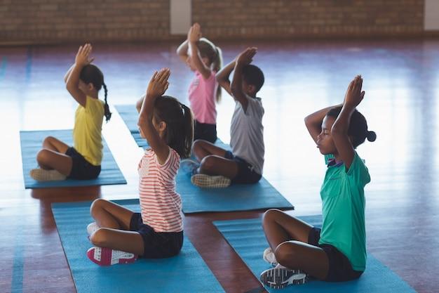 Schoolkinderen mediteren tijdens yogales