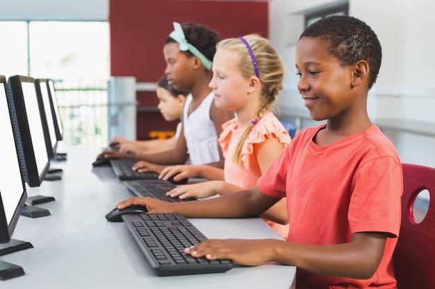 Schoolkinderen met behulp van computer in de klas