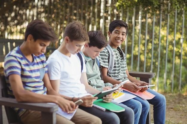 Schoolkinderen met behulp van mobiele telefoon en digitale tablet op de bank