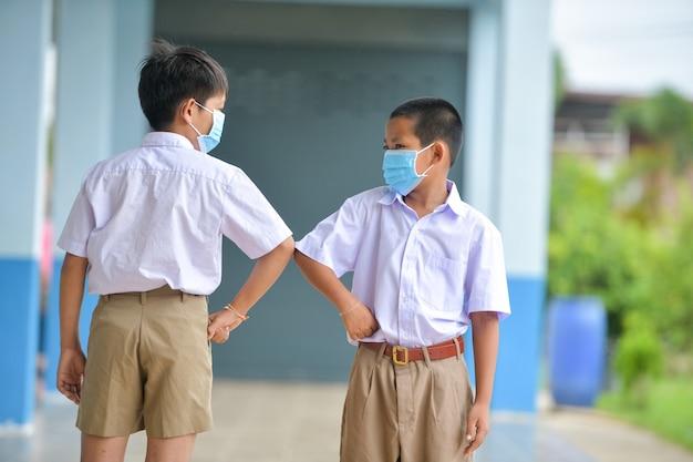 Schoolkinderen met bescherming gezichtsmasker tegen griepvirus bij les in de klas