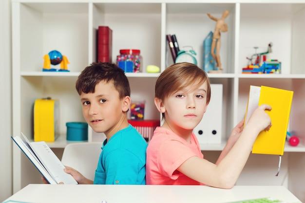 Schoolkinderen met boeken in de klas. kinderen denken over nieuw schoolproject. terug naar schoolconcept.