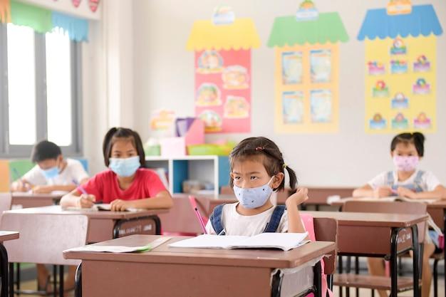 Schoolkinderen met gezichtsmasker bescherming tegen griepvirus bij les in de klas