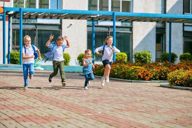 Schoolkinderen met rugzakken die uit school raken