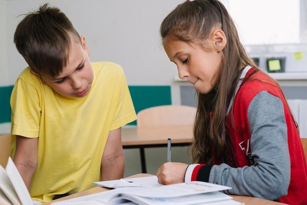Schoolkinderen schrijven in de klas