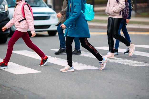 Schoolkinderen steken de weg over in medische maskers. kinderen gaan naar school.