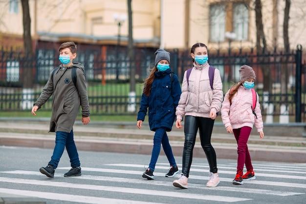 Schoolkinderen steken de weg over in medische maskers