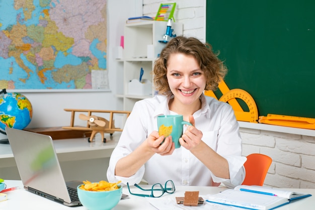Schoolleraar die in klaslokaal eet. lunchtijd. onderwijsconcept. studeren en leren.