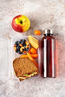 Schoolmaaltijddoos met veganistische sandwichnoten en bessen op grijze concrete achtergrond