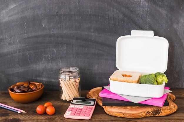 Schoolmateriaal en voedsel dichtbij bord