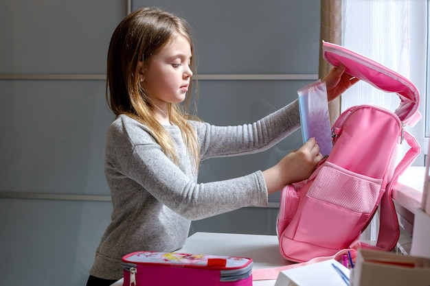 Schoolmeisje bereidt zich voor op school, haar rugzak verzamelt boeken in een schooltas