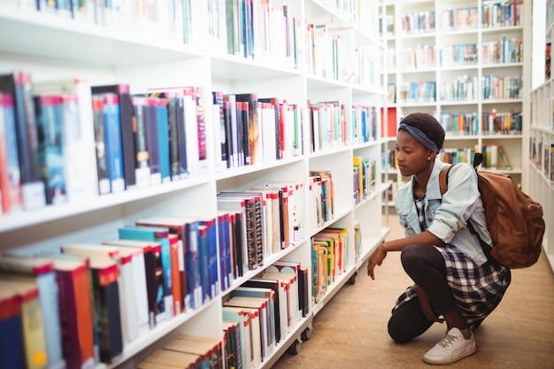 Schoolmeisje boek selecteren uit boekenplank in bibliotheek