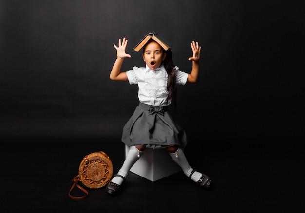 Schoolmeisje brunette met een boek op haar hoofd hief emotioneel haar handen omhoog