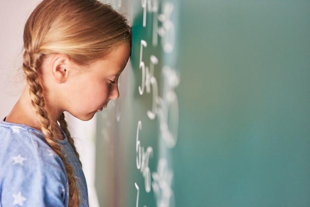 Schoolmeisje dat formule probeert te begrijpen