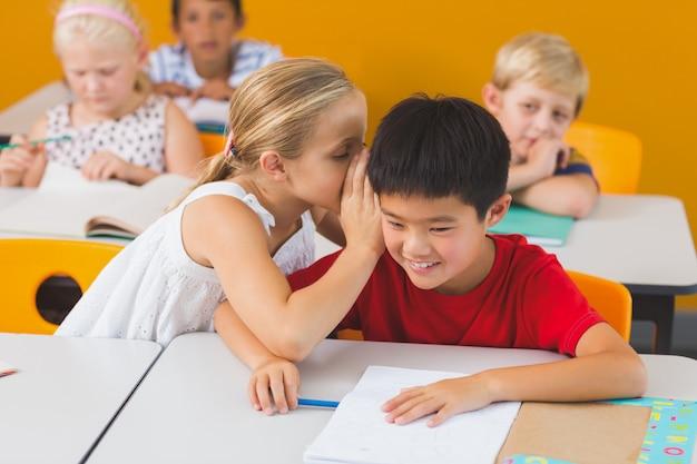 Schoolmeisje dat in het oor van haar vriend in klaslokaal fluistert