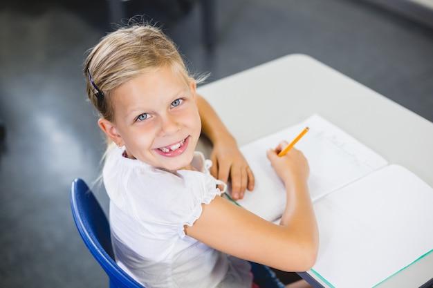 Schoolmeisje dat in klaslokaal glimlacht