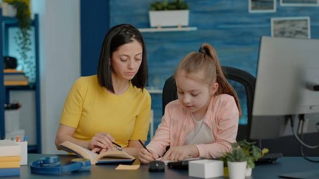 Schoolmeisje dat op notitieboekje schrijft en boek controleert op informatie