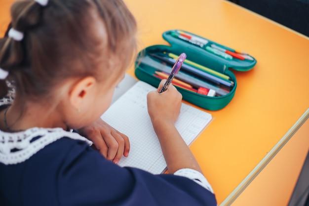 Schoolmeisje dat op schoolbook in haar klaslokaal schrijft