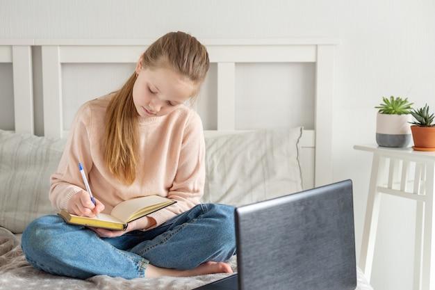 Schoolmeisje dat thuis met behulp van laptop bestudeert. online onderwijs, quarantaineconcept