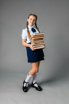 Schoolmeisje dat zware leerboeken op gele studioachtergrond houdt