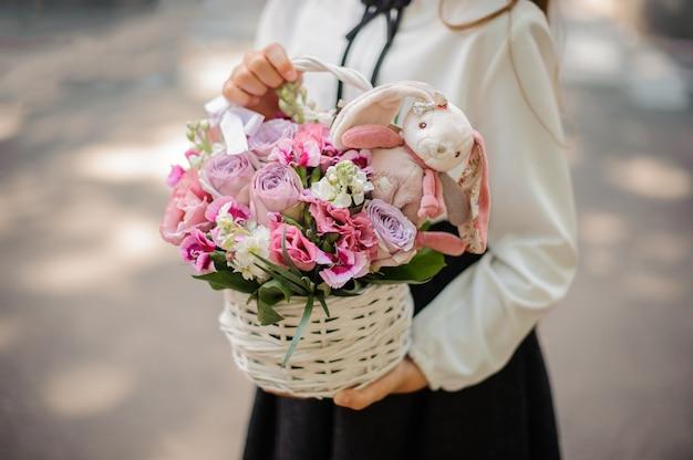 Schoolmeisje die een leuk rieten mandhoogtepunt van heldere roze bloemen houden die met een stuk speelgoed worden verfraaid
