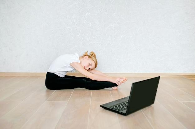 Schoolmeisje die online video op laptop bekijken en sportoefeningen doen - yoga, gymnastiek, choreografie. blijf thuis. concept van zelfisolatie, quarantaine, online onderwijs.