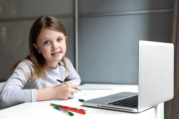 Schoolmeisje doet haar huiswerk met laptopcomputer thuis op zoek