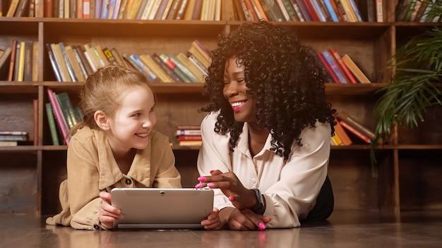 Schoolmeisje en babysitter kijken naar het tabletscherm en lachen