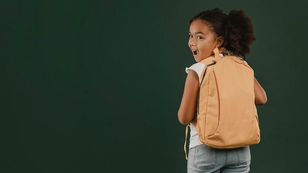 Schoolmeisje en haar rugzak kopiëren ruimte