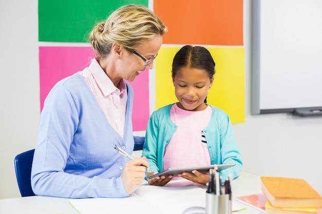 Schoolmeisje en leraar die digitale tablet in klaslokaal gebruiken